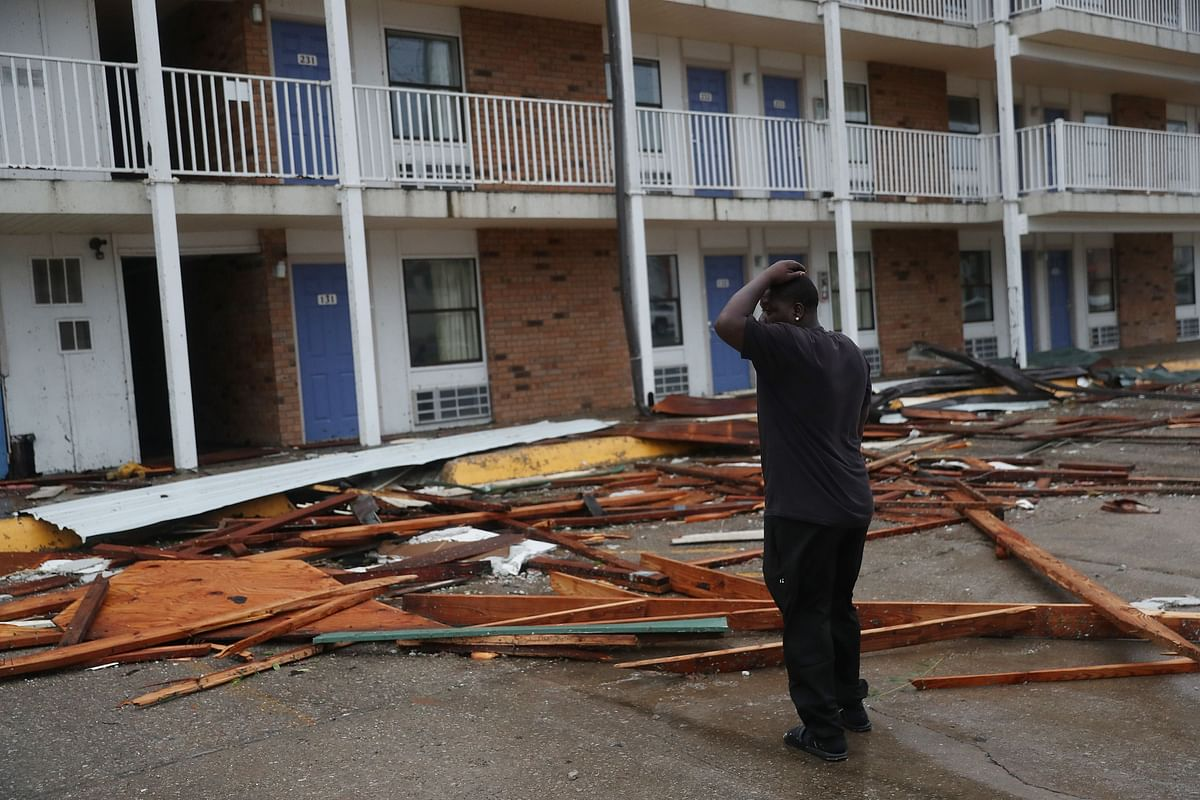 A person stands next to a hotel that had parts of its roof blown off as Hurricane Laura passed through the area on August 27, 2020 in Lake Charles, Louisiana .