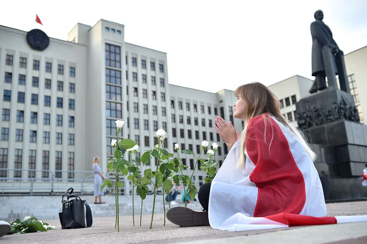 A woman covered by a Belarus flag sits near the Government House in Independence Square during a protest rally against police violence.