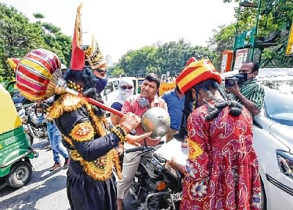 Dressed as 'Yamraj' and 'Chitragupta', officials stop a biker for not wearing a mask as part of an awareness campaign to curb  COVID-19 spread in New Delhi on Monday.