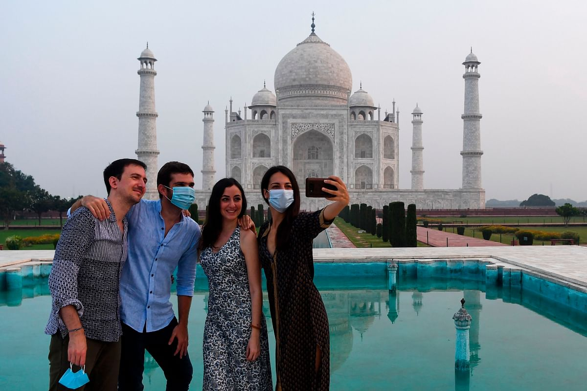 Tourists have their pictures taken at the Taj Mahal in Agra on September 21, 2020. - The Taj Mahal reopens to visitors on September 21 in a symbolic business-as-usual gesture, even as India looks set to overtake the US as the global leader in coronavirus infections.