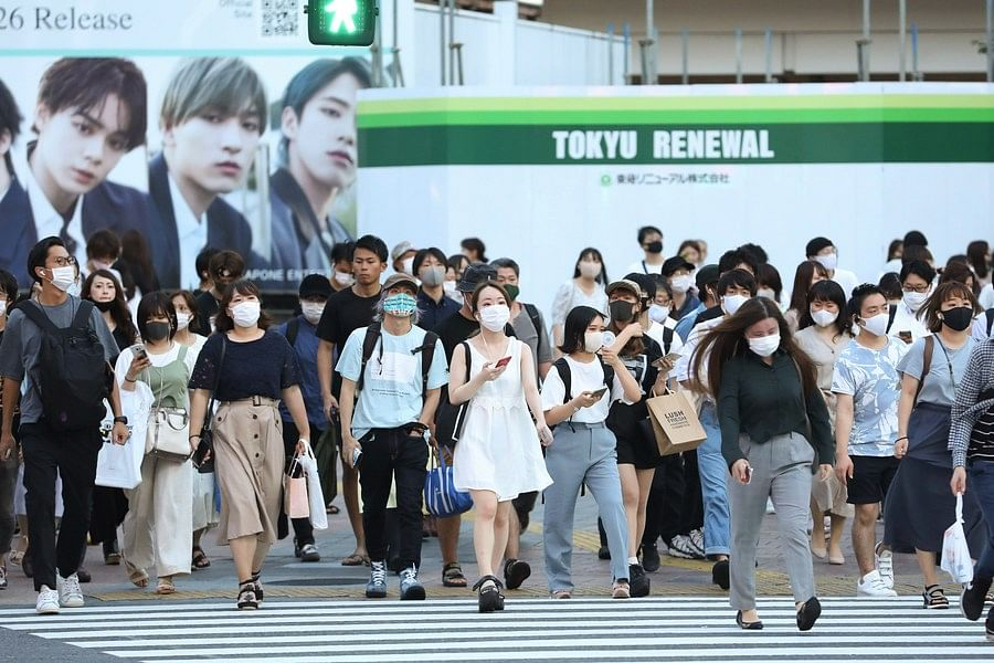 People wearing face masks walk on the street at Shibuya in Tokyo, Japan, on Aug. 20, 2020.
