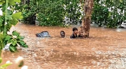 Two men stuck in a waterlogged area wait for the NDRF team's help to get rescued following  heavy rainfall in Udupi district of Karnataka on Sunday.