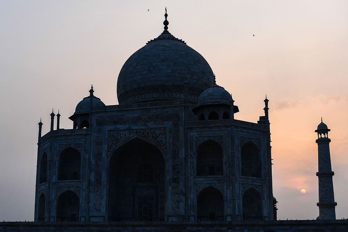 The sun rises behind the Taj Mahal in Agra on September 21, 2020. - The Taj Mahal reopens to visitors on September 21 in a symbolic business-as-usual gesture, even as India looks set to overtake the US as the global leader in coronavirus infections.