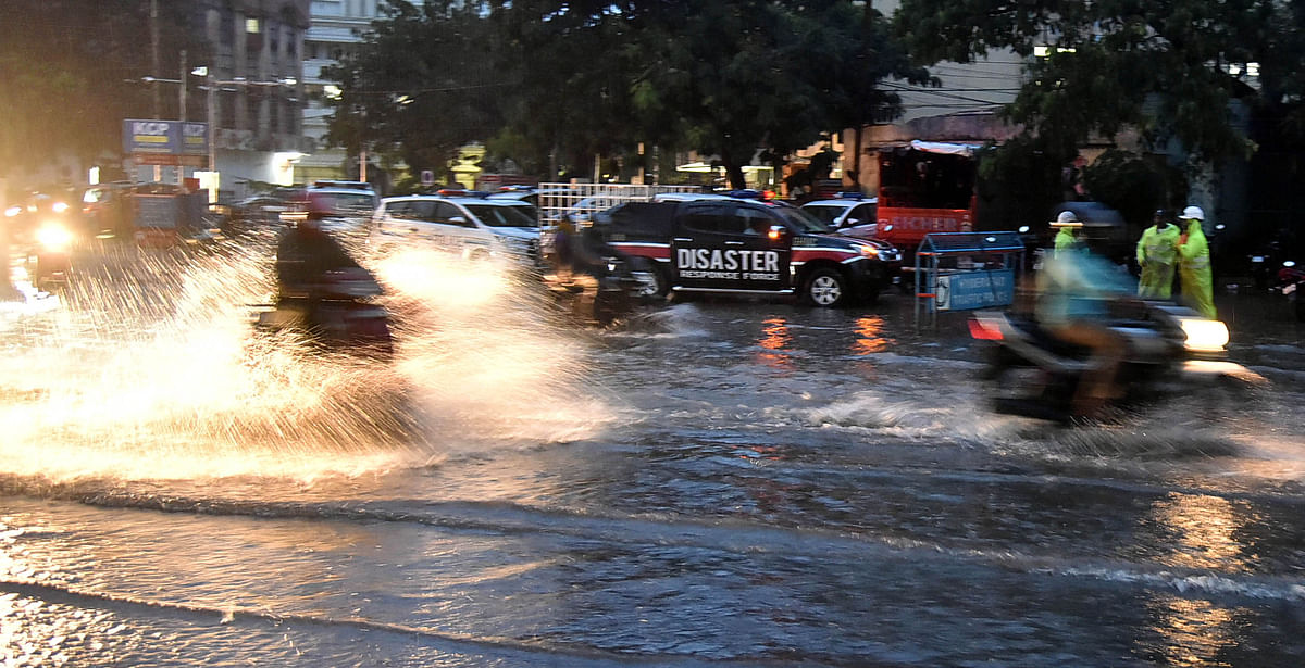 Vehicles wade through a flooded street after heavy rain, in Hyderabad on Wednesday
