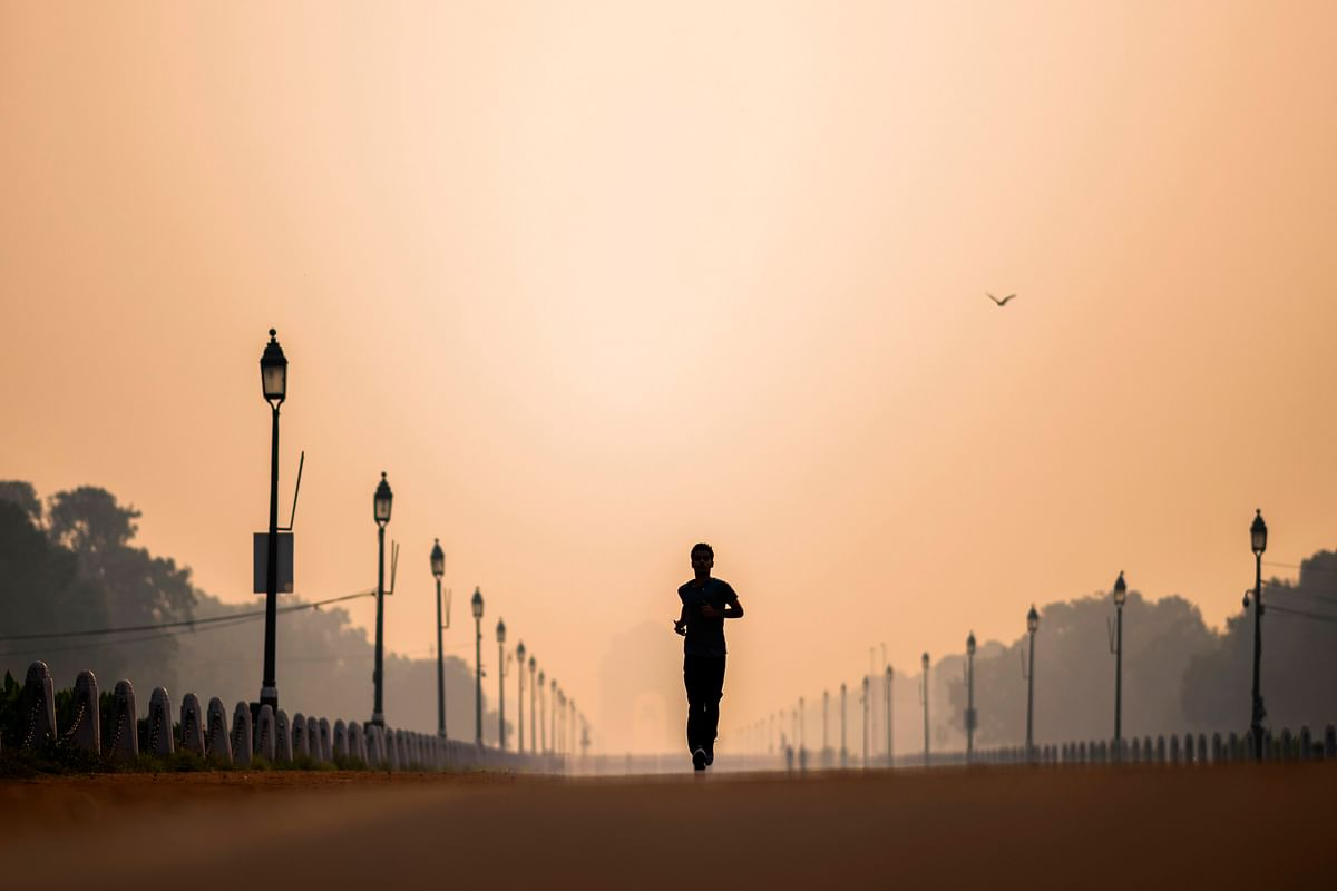 A man jogs along Rajpath street during a smoggy morning in New Delhi on October 15, 2020.