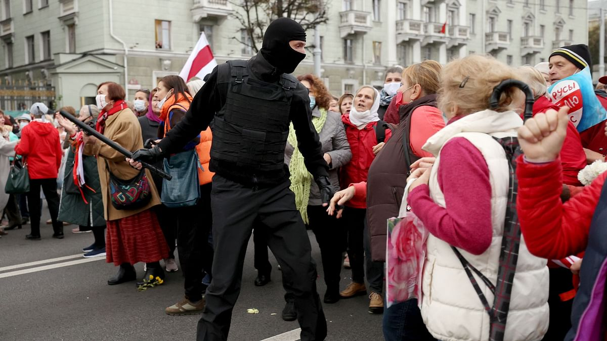 Belarusian pensioners argue with a law enforcement officer during a rally to demand the resignation of authoritarian leader and new fair election in Minsk on October 12, 2020