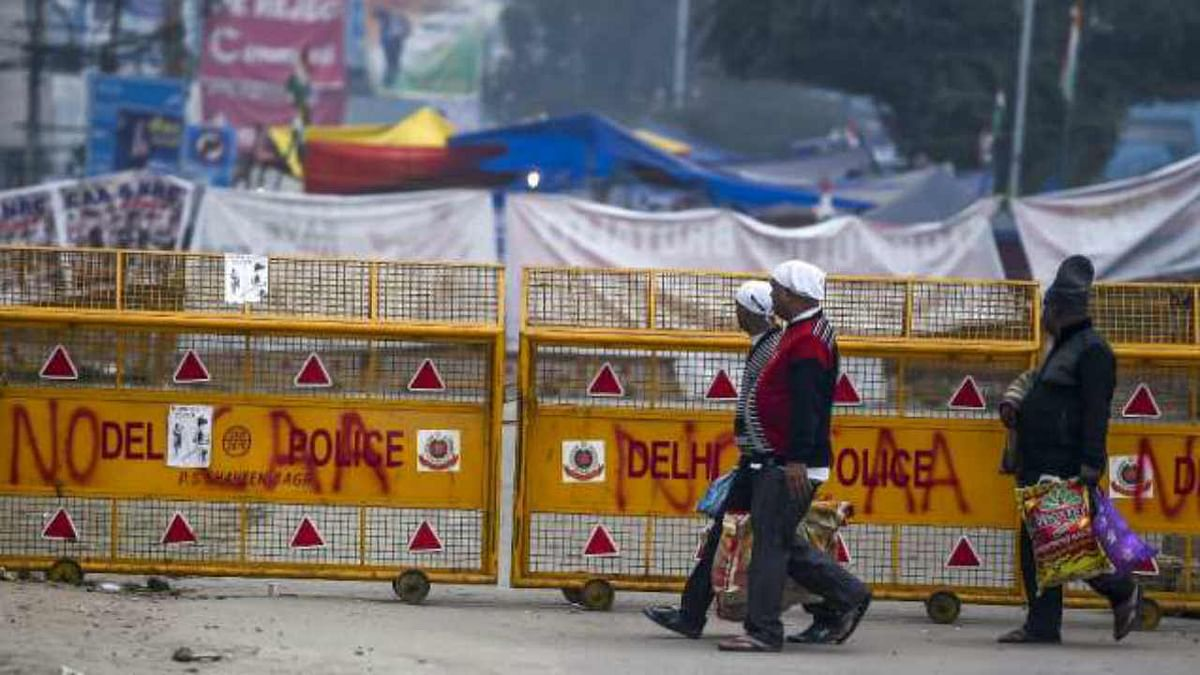 People walk past barricades at protests site in Delhi's Shaheen Bagh