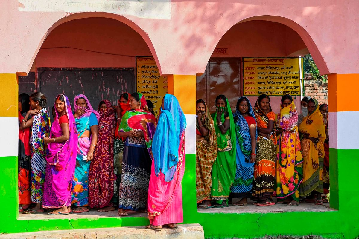 Voters queue up to cast their ballots in the first phase of Bihar assembly elections, in Masaurhi on Wednesday