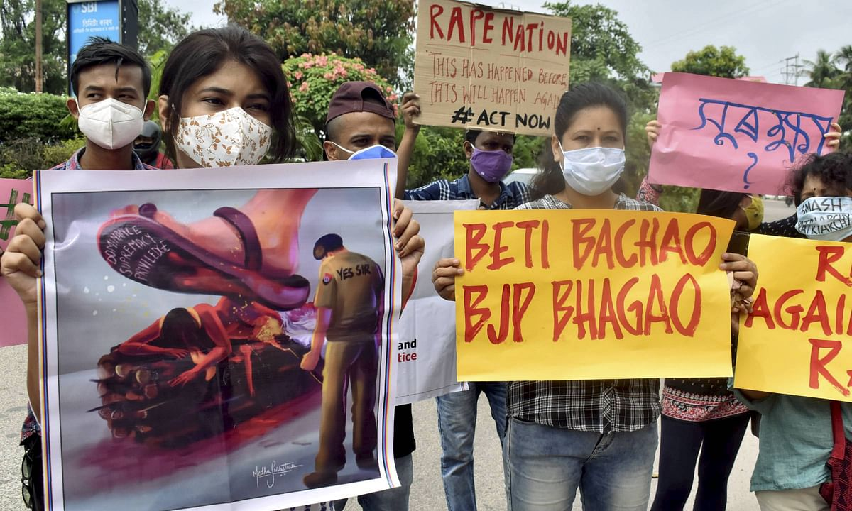 Activists hold placards during a protest over the death of a 19-year-old Dalit woman after an alleged gangrape in UPs Hathras, in Guwahati, Saturday, Oct. 3, 2020.