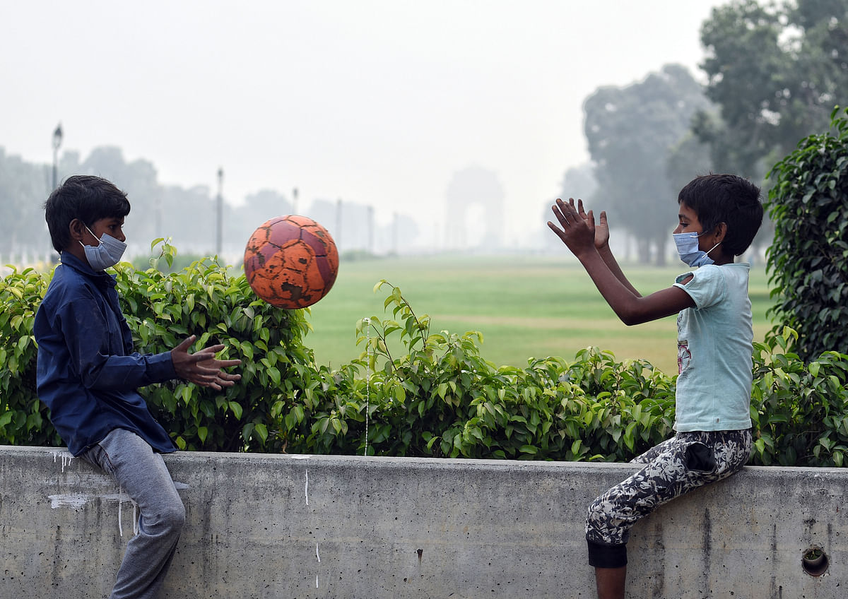 Two children play with a ball in a smoggy morning as the air quality deteriorates.