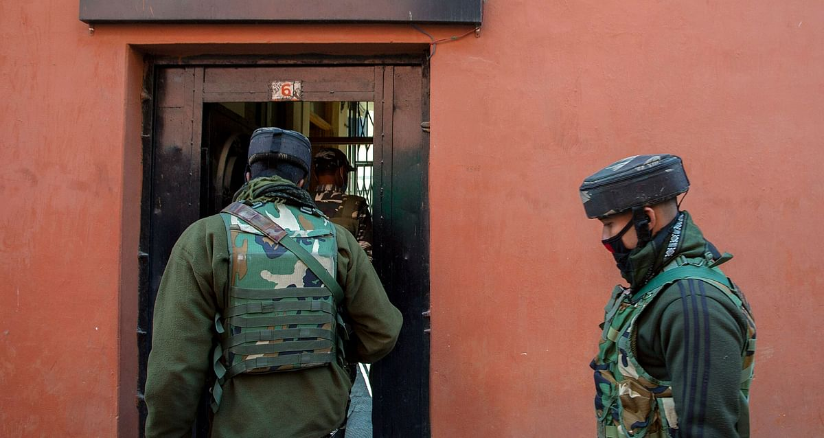 NIA members carry out a raid at the Greater Kashmir office, in Srinagar on Wednesday