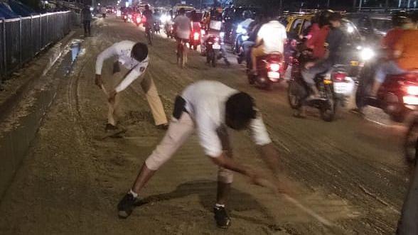 Dadar traffic cops take spades and clear fallen cement on Tilak Bridge