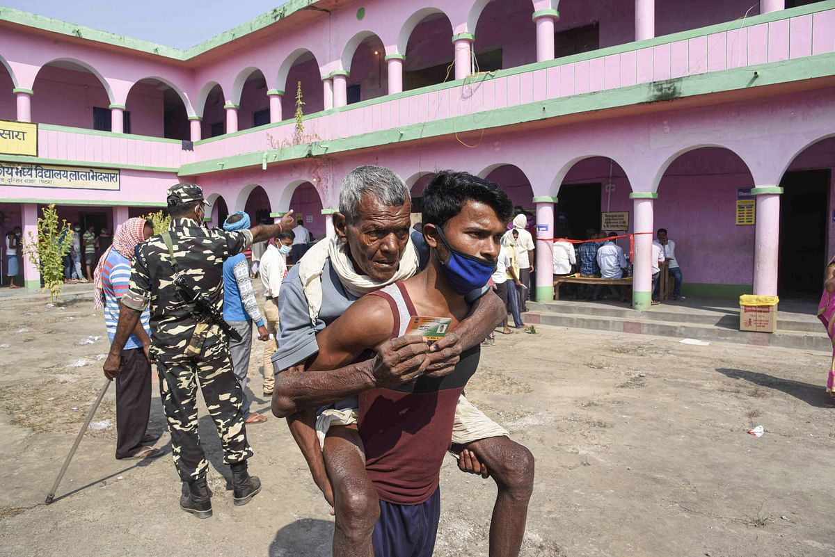 An old man on the back of his son leaves after they cast their votes in the first phase of Bihar Assembly Elections, at Paliganj constituency in Patna on Wednesday