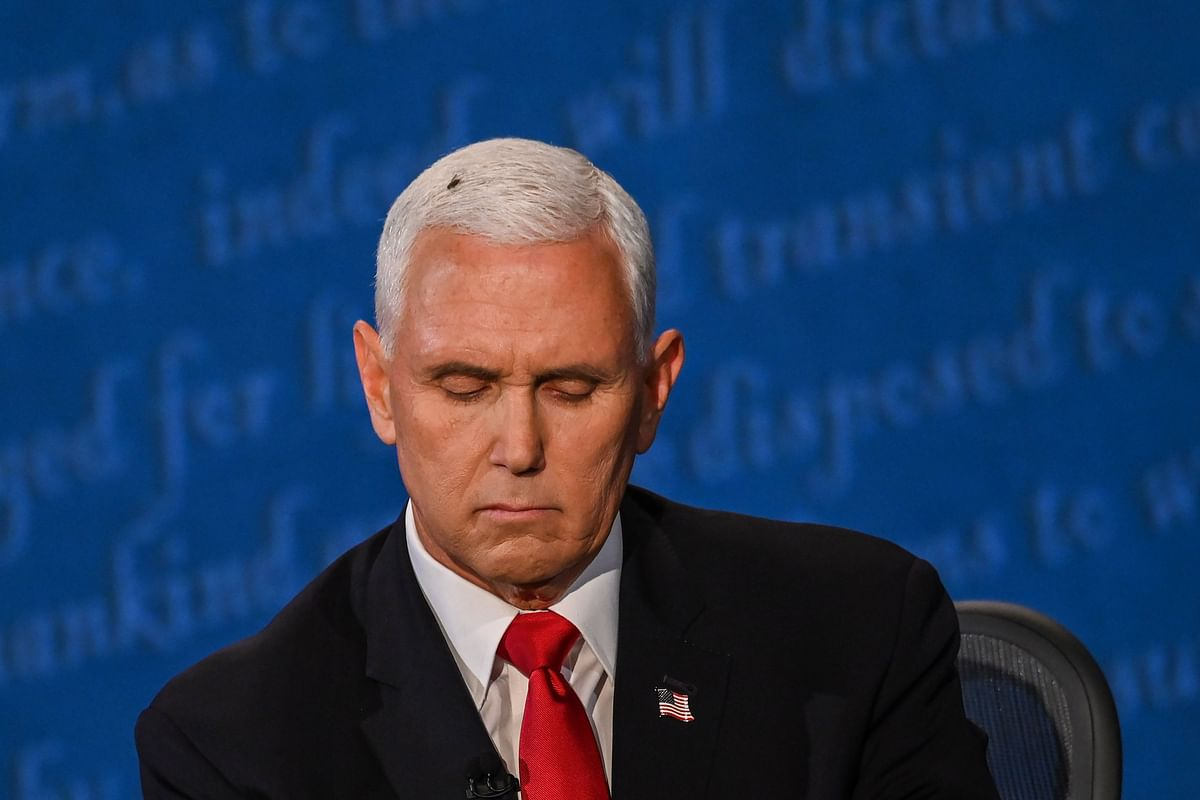 A fly rests on the head of US Vice President Mike Pence as he takes notes during the vice presidential debate against Kamala Harris
