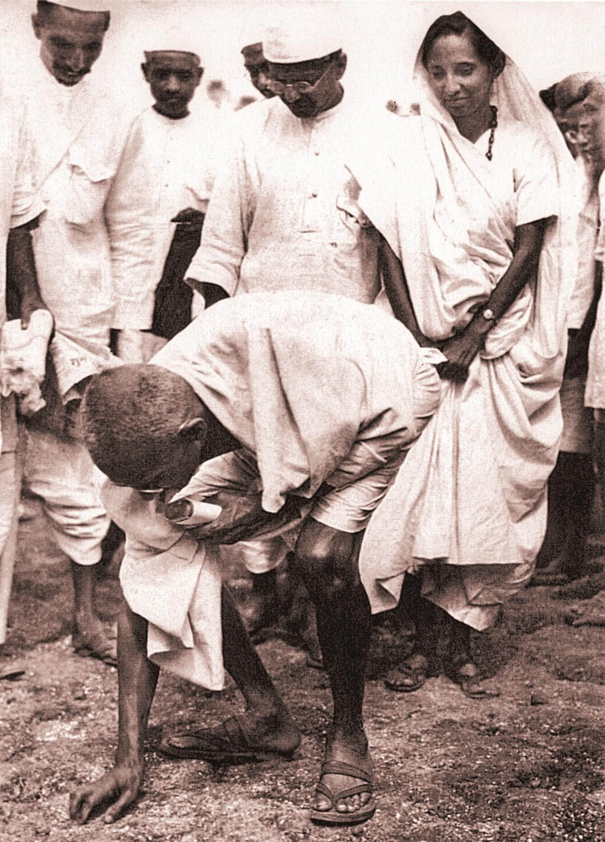 Gandhi ceremoniously breaking the salt law by picking up a lump of natural salt at Dandi on Apirl 6, 1930