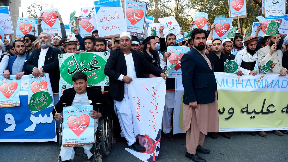 Muslim demonstrators hold banners as they shout slogans during a protest in downtown Kabul