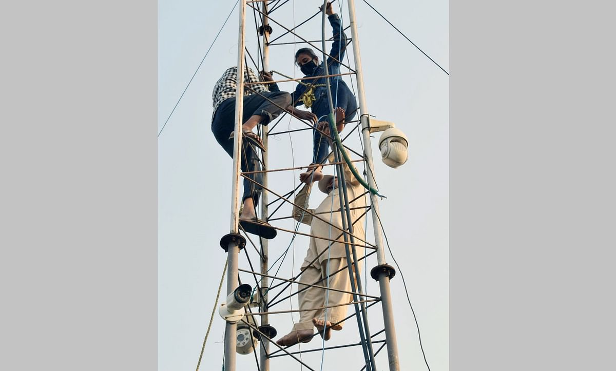 BMC workers rescue a woman Sunita Thapa, who climbed a tower attempt to commit suicide after being allegedly harassed by a police driver and being unheard of complaining to the police, near CMs residence in Bhopal on Friday.