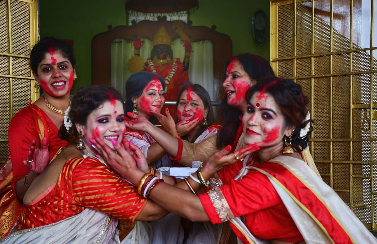 Members of Satya Sai Group applying vermilion on  one another at Kalibari, Kolar Road in the city on Monday