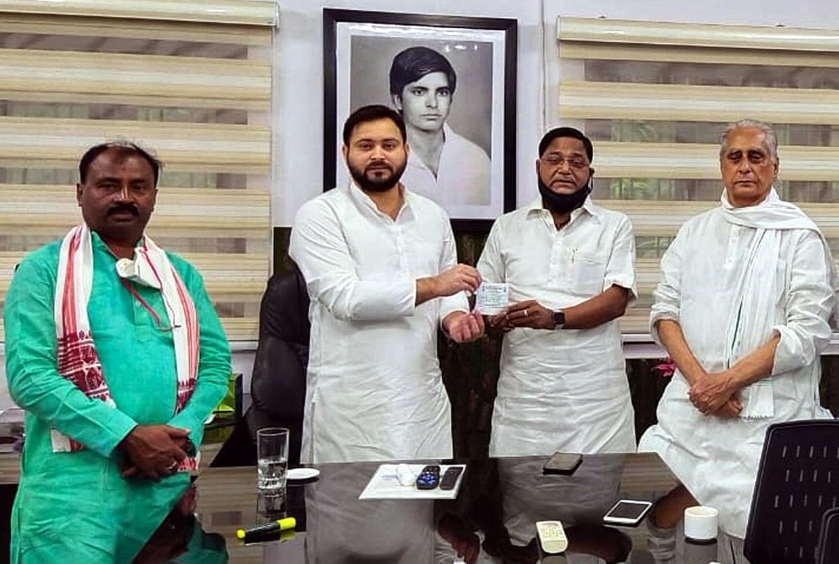 RJD leader Tejashwi Yadav presents party member slip to JD-U senior leader Vishwa Mohan Mandal as he joins the party in Patna on Monday.