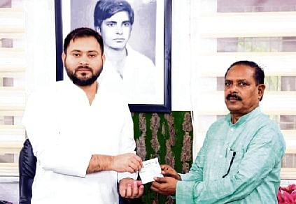 Tejashwi Yadav presents RJD membership slip to BSP state chief Bharat Bind as he joins former's party in Patna on Saturday.