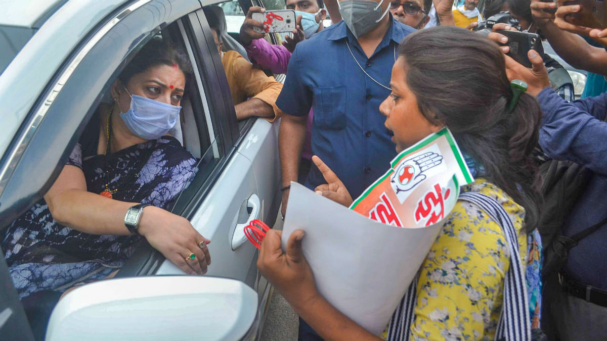 A Congress party activist protests near the vehicle of Union Minister Smriti Irani, over the death of a 19-year-old Dalit woman after an alleged gangrape in UP's Hathras