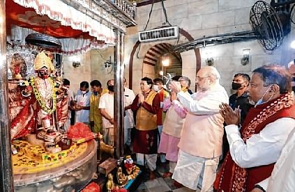 Home Minister Amit Shah offers prayers; and (bottom) a woman touches his feet at Dakshineswar Temple in Kolkata on Friday.