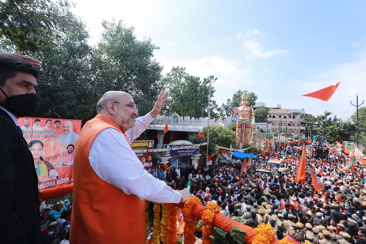 Union Home Minister Amit Shah waves to his supporters during his roadshow in Hyderabad.