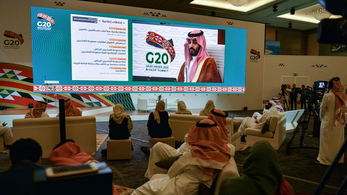 Media persons gathered at the International Media Centre in Saudi Arabias capital Riyadh on November 21, 2020 watch on a projected screen as Saudi Crown Prince Mohammed bin Salman attends the G20 summit, held virtually due to the COVID-19 coronavirus pandemic. - Saudi Arabia opened the G20 summit on November 21 in a first for an Arab nation, with the virtual forum dominated by efforts to tackle the coronavirus pandemic and the worst global recession in decades. The two-day meeting of the worlds wealthiest nations comes as President Donald Trump refuses to concede a bitter election and campaigners criticise what they call the G20s inadequate response to the crippling economic crisis.