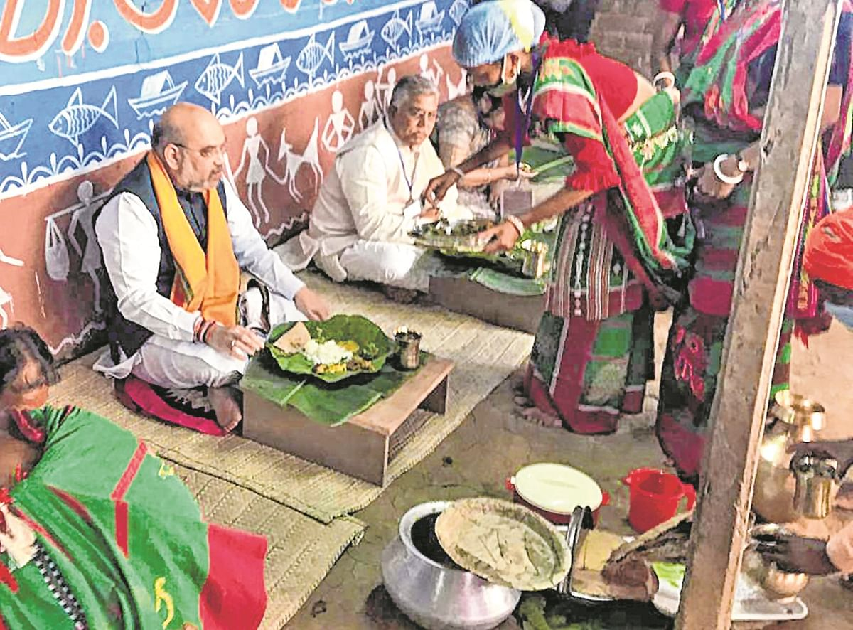 Union Home Minister Amit Shah having food at the house of a tribal family in Bankura on Thursday.