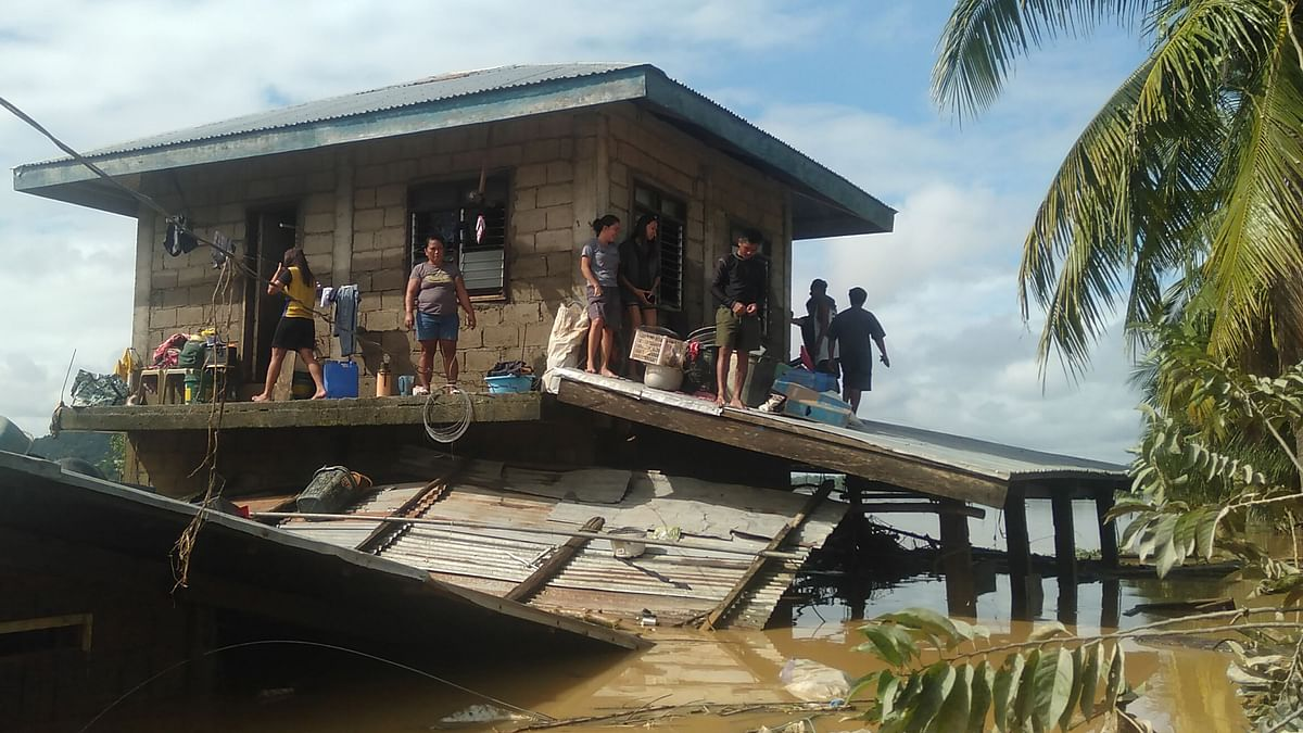 Residents shelter on the second floor of their house surrounded by floodwaters in the town of Ilagan in Isabela province, north of Manila on November 14, 2020, two days after Typhoon Vamco hit parts of the country bringing heavy rains and flooding.