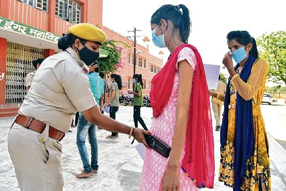 A lady cop frisks an applicant as she arrives for the Rajasthan  police constable recruitment exam 2020 in Bikaner on Sunday.