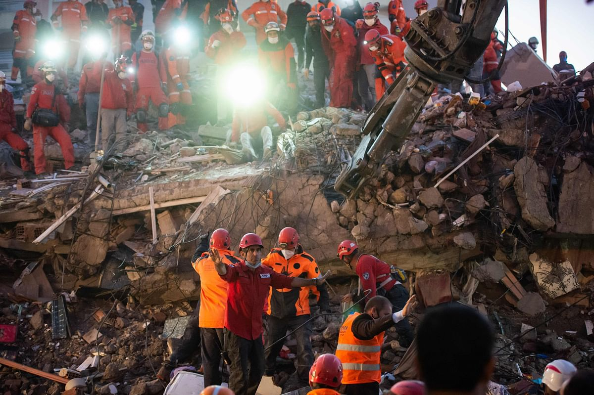 Volunteers search for survivors in a collapsed building in Izmir, on October 31, 2020, after a powerful earthquake struck Turkeys western coast and parts of Greece.