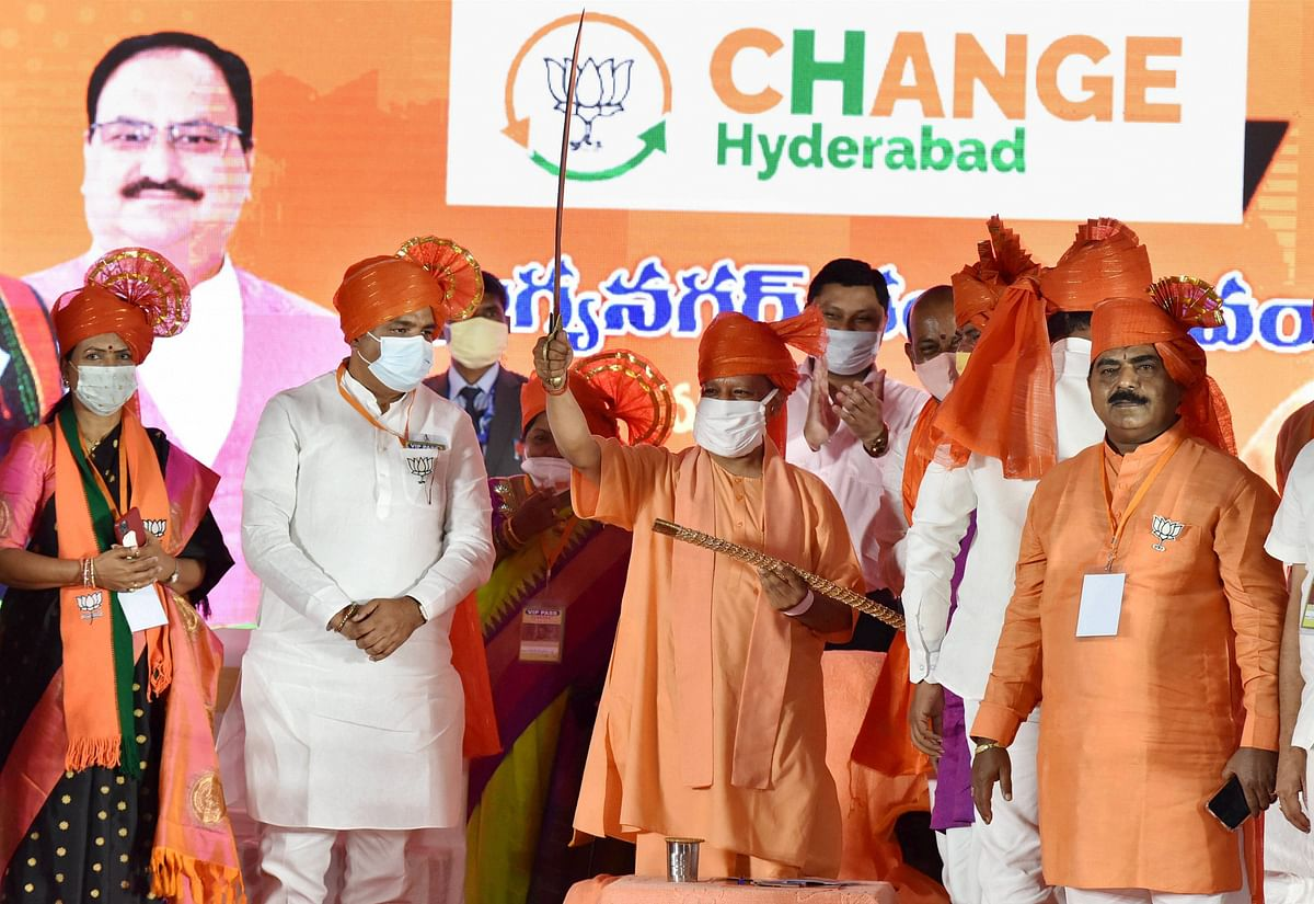 Uttar Pradesh Chief Minister Yogi Adityanath, flanked by BJP Telangana leaders, holds a sword during a public meeting, ahead of GHMC elections in Hyderabad.