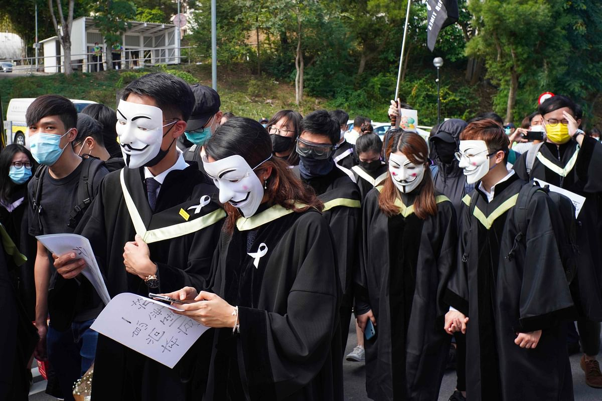 Students from the Chinese University of Hong Kong (CUHK), wearing graduation gowns and and masks, take part in a protest march and display slogans that authorities say are now illegal under the new security law.