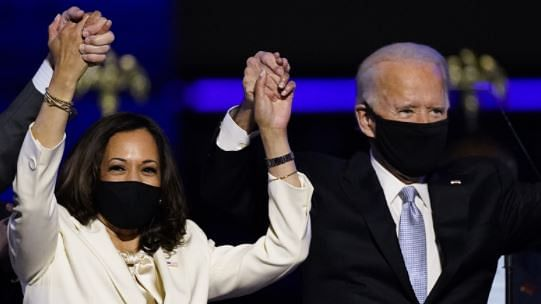 Vice President-elect Kamala Harris holds hands with President-elect Joe Biden and her husband Doug Emhoff as they celebrate Saturday, Nov. 7, 2020, in Wilmington, Delaware
