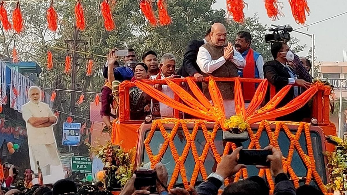 Union Home Minister Amit Shah greets his supporters during a roadshow in Bolpur on Sunday.