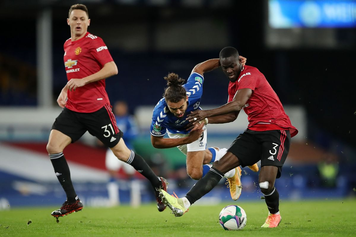 Manchester United's Ivorian defender Eric Bailly (R) tackles Everton's English striker Dominic Calvert-Lewin (C) during the English League Cup quarter final against  Everton