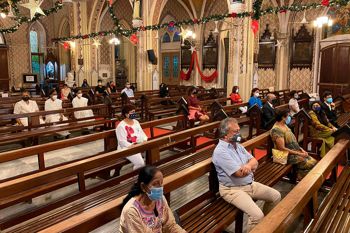 Christian devotees take part in a mass service on the eve of Christmas, in Mumbai on December 24, 2020