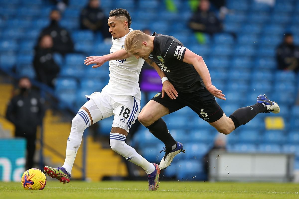 Leeds United's Brazilian midfielder Raphinha (L) vies with Burnley's English defender Ben Mee (R) during the English Premier League football against Burnley at Elland Road in Leeds, on Sunday