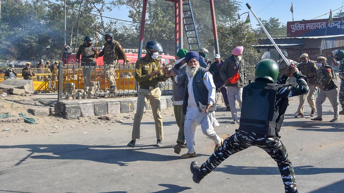 A security person baton charges on a farmer as protestors cross Singhu border during Delhi Chalo protest march against the new farm laws, in New Delhi, Friday, November 27, 2020