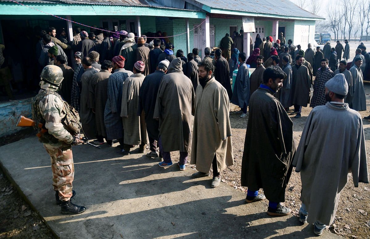 Voters stand in a queue to cast their votes for the 8th phase of the DDC elections, at Bandipora in North Kashmir on Saturday.