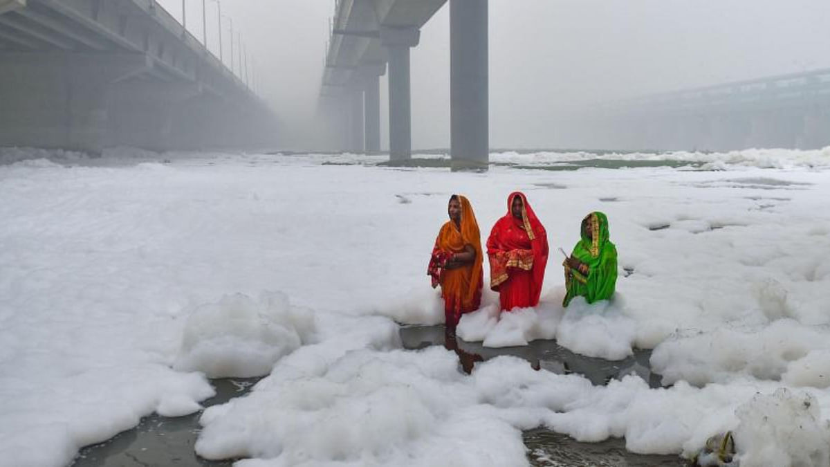 Devotees offer prayer to the rising sun as toxic 'froth' floats on the surface of a polluted Yamuna river
