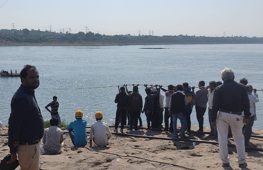 West Discom employees using a boat to change power line passing over Narmada river in Barwaha on Friday.