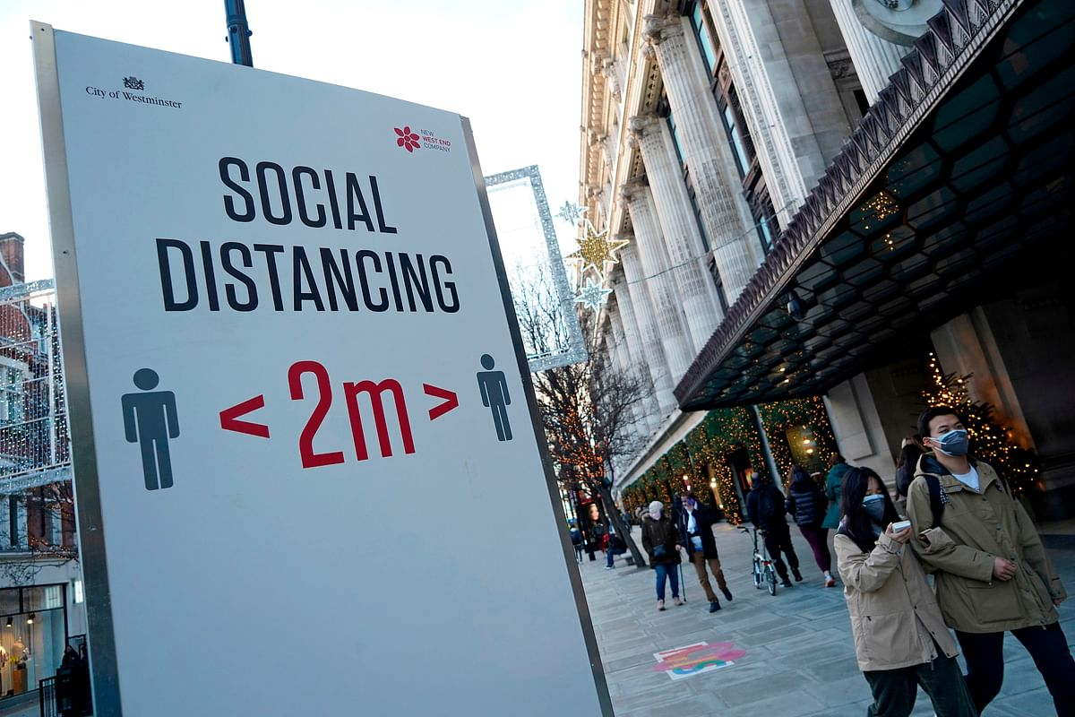 Pedestrians wearing a face mask or covering due to the COVID-19 pandemic, walk past a sign asking people to social distance, on Oxford Street in central London on December 20, 2020.