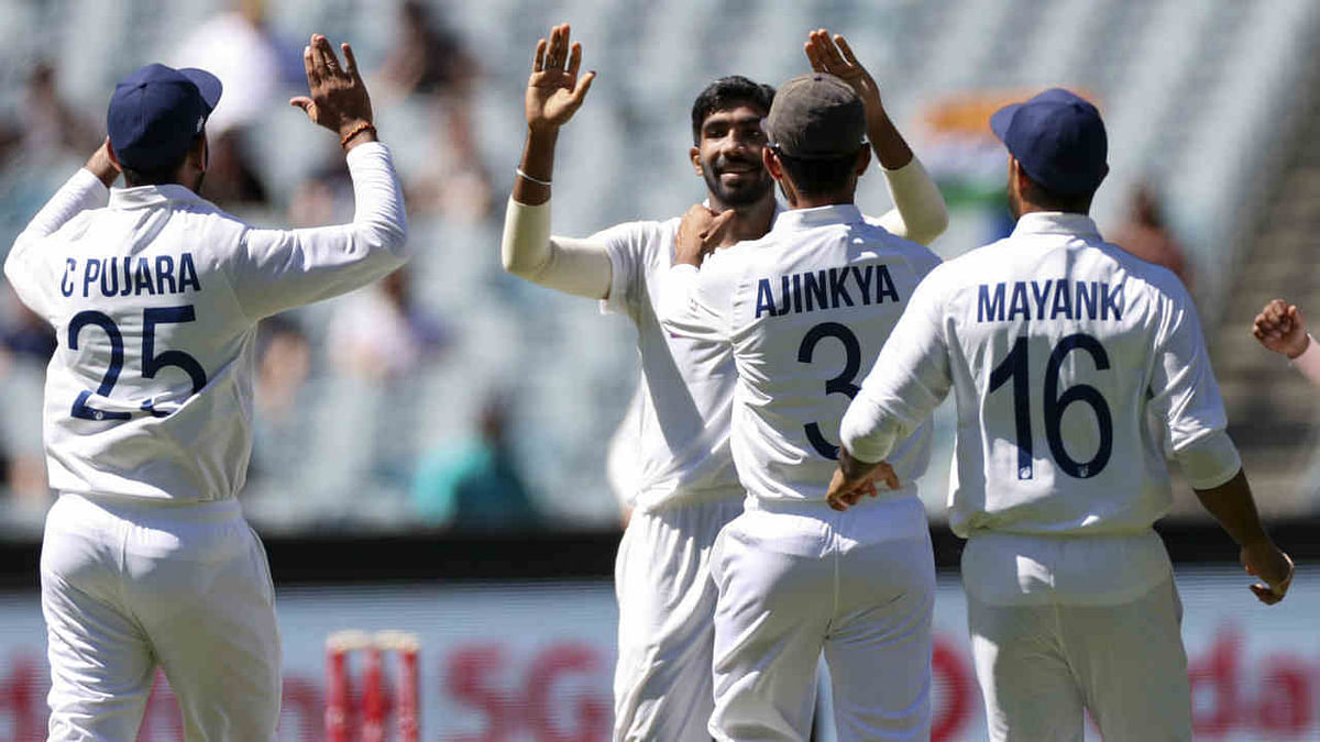 Jasprit Bumrah, centre, is congratulated by teammates after taking the wicket of Australia's Joe Burns on day one of the Boxing Day cricket test between India and Australia at the Melbourne Cricket Ground, Melbourne, Australia, Saturday