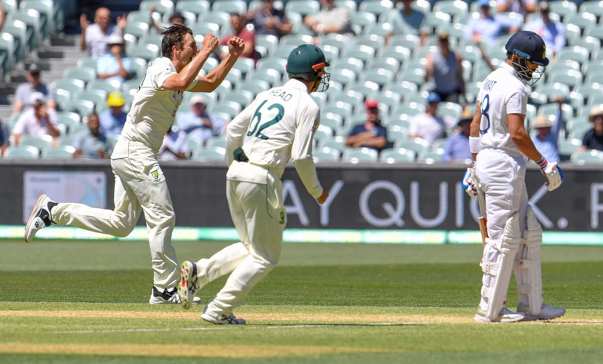 Australias Pat Cummins (L) celebrtaes dismissing Indias Virat Kohli (R) on the third day of the first cricket Test match between Australia and India played in Adelaide on December 19, 2020.