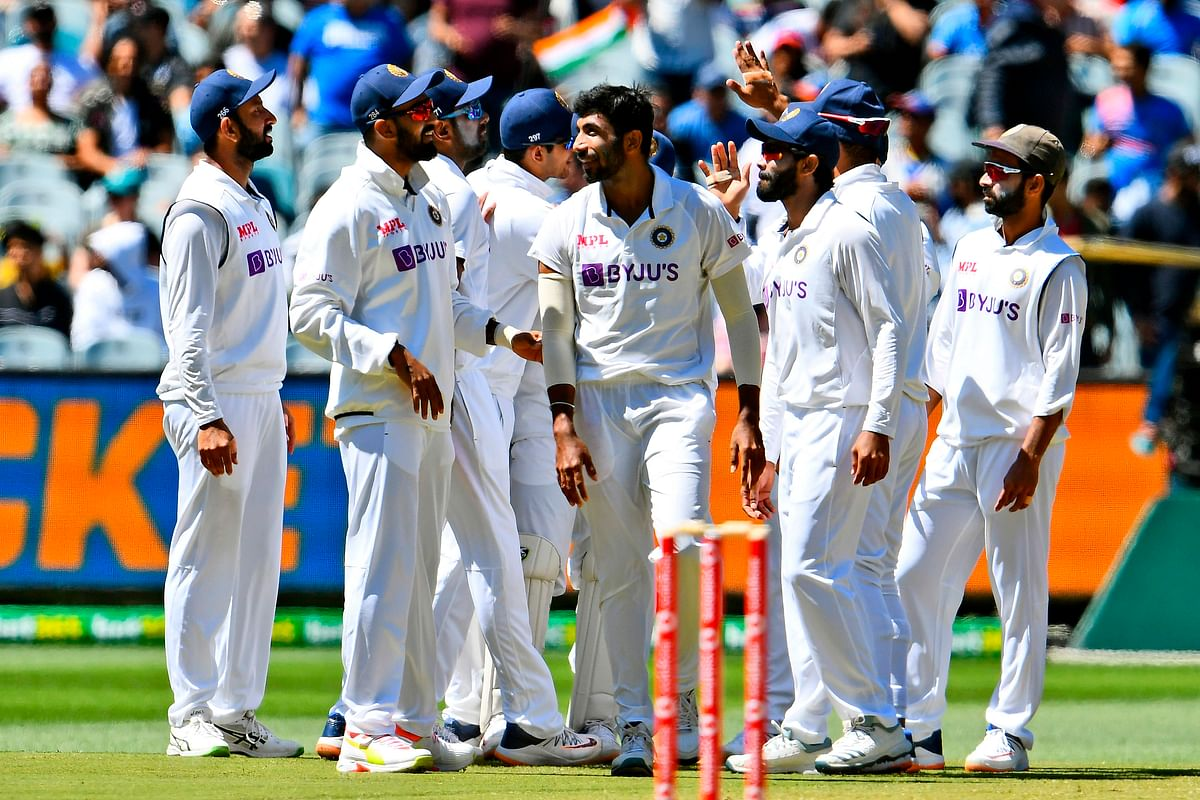 Indian players walk back after knocking out Australia for 200 runs in their second innings