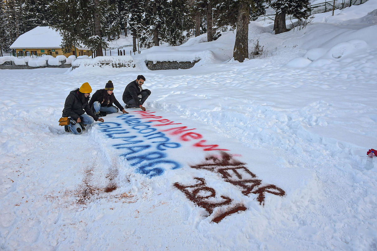 Gulmarg: Tourists sit near Happy New Year 2021 sign on snow at the famous ski resort of Gulmarg in north Kashmir on the eve of the New Year, Thursday, Dec. 31, 2020. The resort is witnessing a huge rush of visitors, with most of them not adhering to social distancing norms and other COVID-19 related precautions.