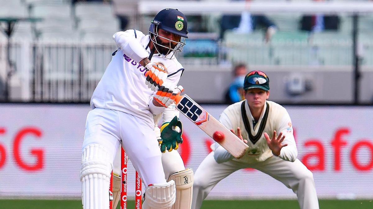 Ravi Jadeja plays a shot as Australias Steve Smith (R) looks on during the day three of the second cricket Test match between Australia and India at the MCG in Melbourne