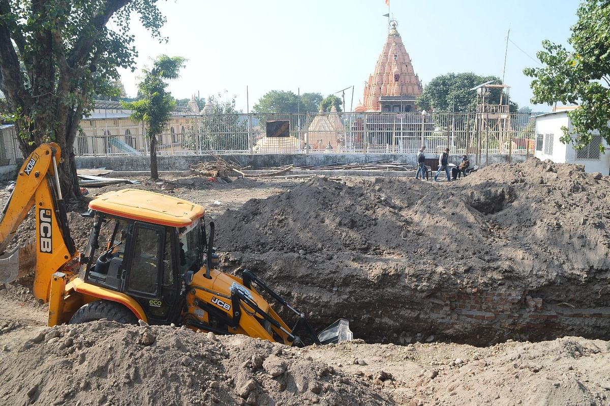 A JCB machine digs the surface at the Mahakal temple complex for the expansion of the temple premises under Smart City Project